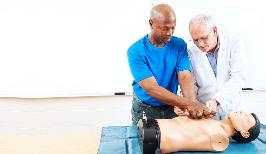 Doctor teaching first aid CPR techniques to an adult