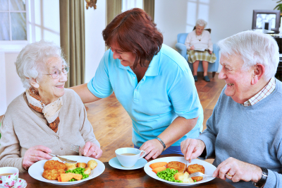 Caregiver serving meal to an elderly seniors
